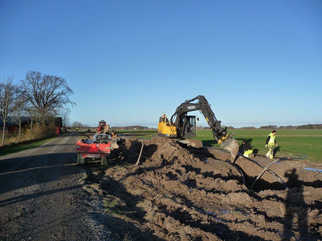 En gul grävmaskin och en röd kedjegrävare i arbete i kanten av en åker bredvid en grusväg.
