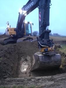 Gul grävmaskin som gräver i jorden.
