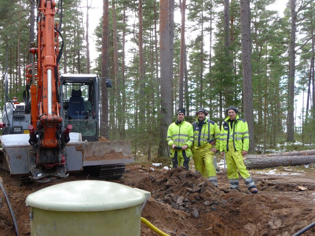 Till vänster i bilden syns en grävmaskin. Till höger står tre män i signalgula arbetskläder. I förgrunden syns överdelen av en pumpstation. Bakom grävmaskinen och männen växer tallar.