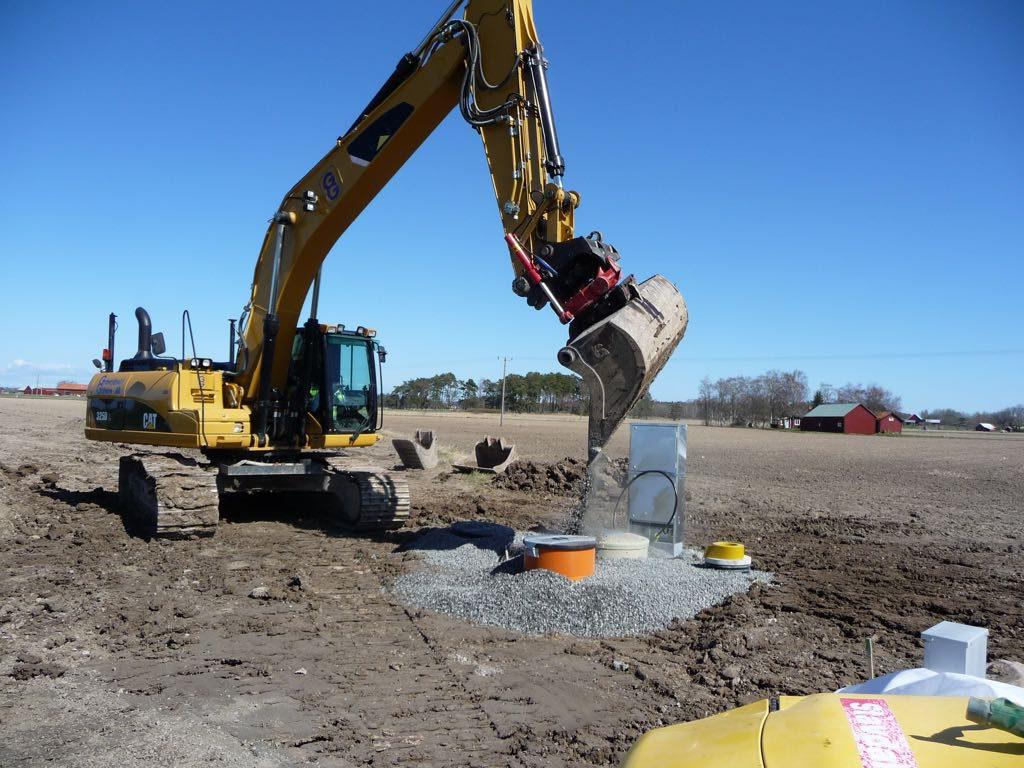 En grävmaskin vars skopa släpper ner grus intill ett grovt, orange rör, som sticker upp en liten bit ovanför marken. Arbetet är nästan klart och vädret är vackert med klarblå himmel.