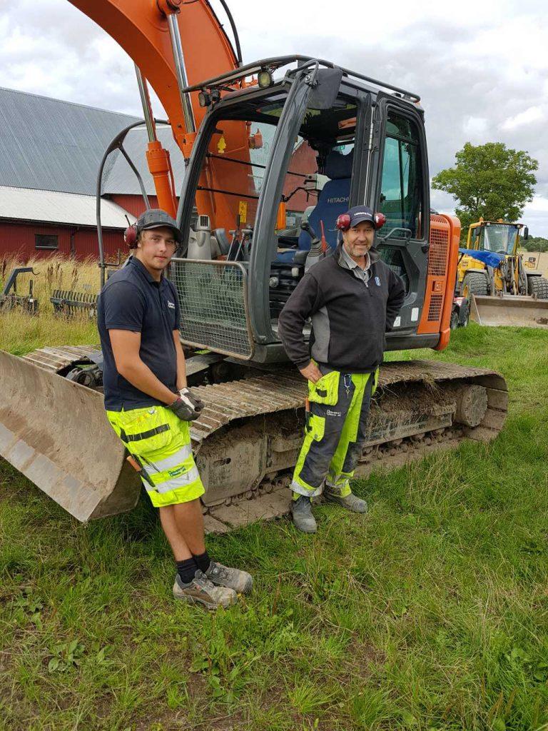 Två glada män från Götene Grävtjänst står på en gräsmatta vid en gräv- och schaktmaskin.