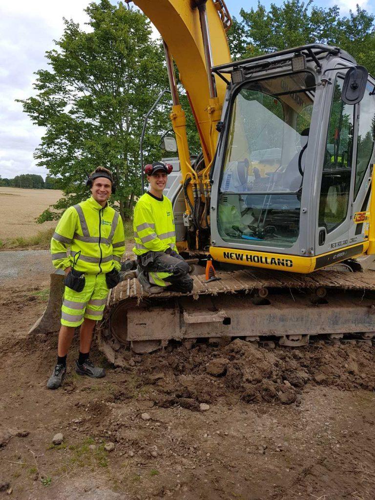Två glada män från Götene Grävtjänst vid en grävmaskin av märket New Holland.